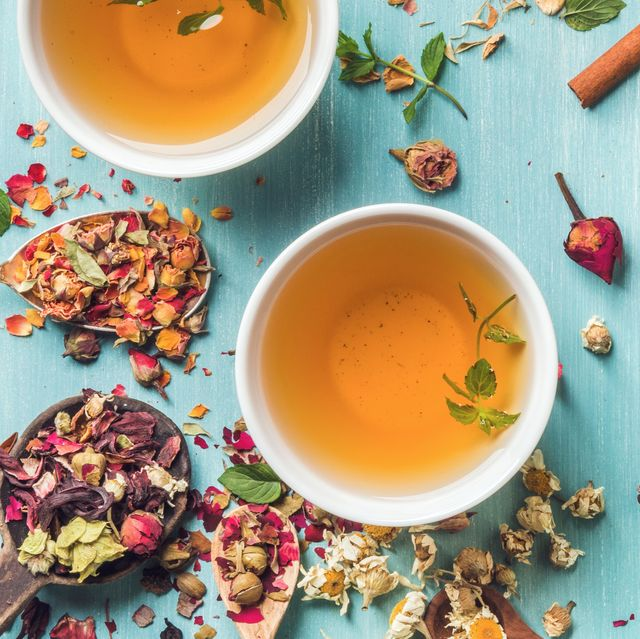 two cups of healthy herbal tea with mint, cinnamon, dried rose, camomile flowers in spoons and man's hand holding spoon