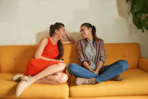 Two diverse women talk on couch