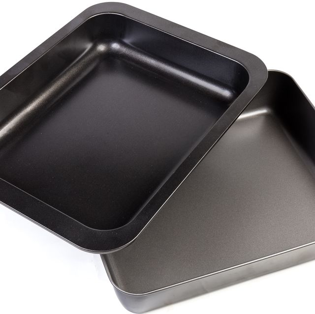 two empty rectangular nonstick oven trays on white background