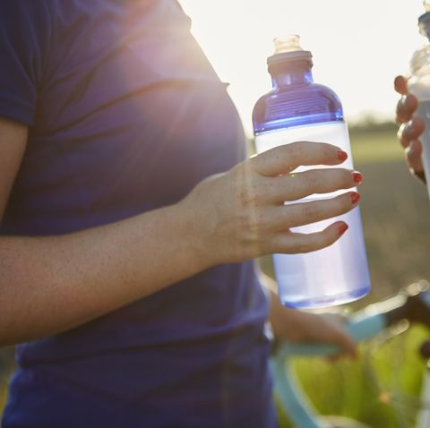 two female cyclists holding water bottles, mid section