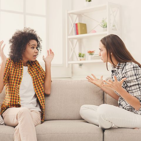 two female friends sitting on sofa and arguing