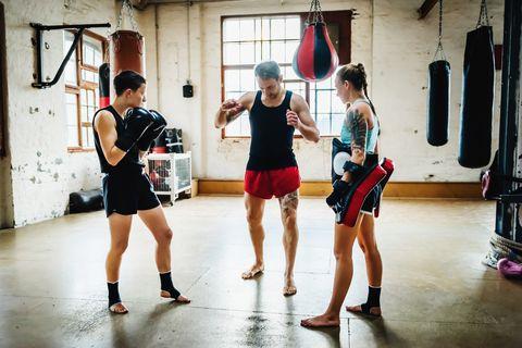 dos luchadoras de muay thai con su entrenador