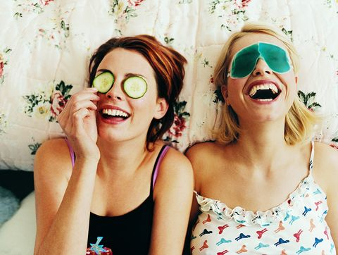 two female teenagers lying in bed wearing eye masks