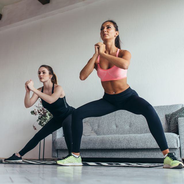 two fit girls doing home workout performing lateral lunges at home