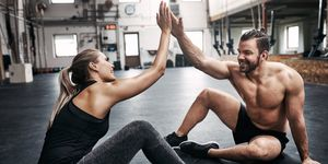 Two fit young people high fiving together after a workout