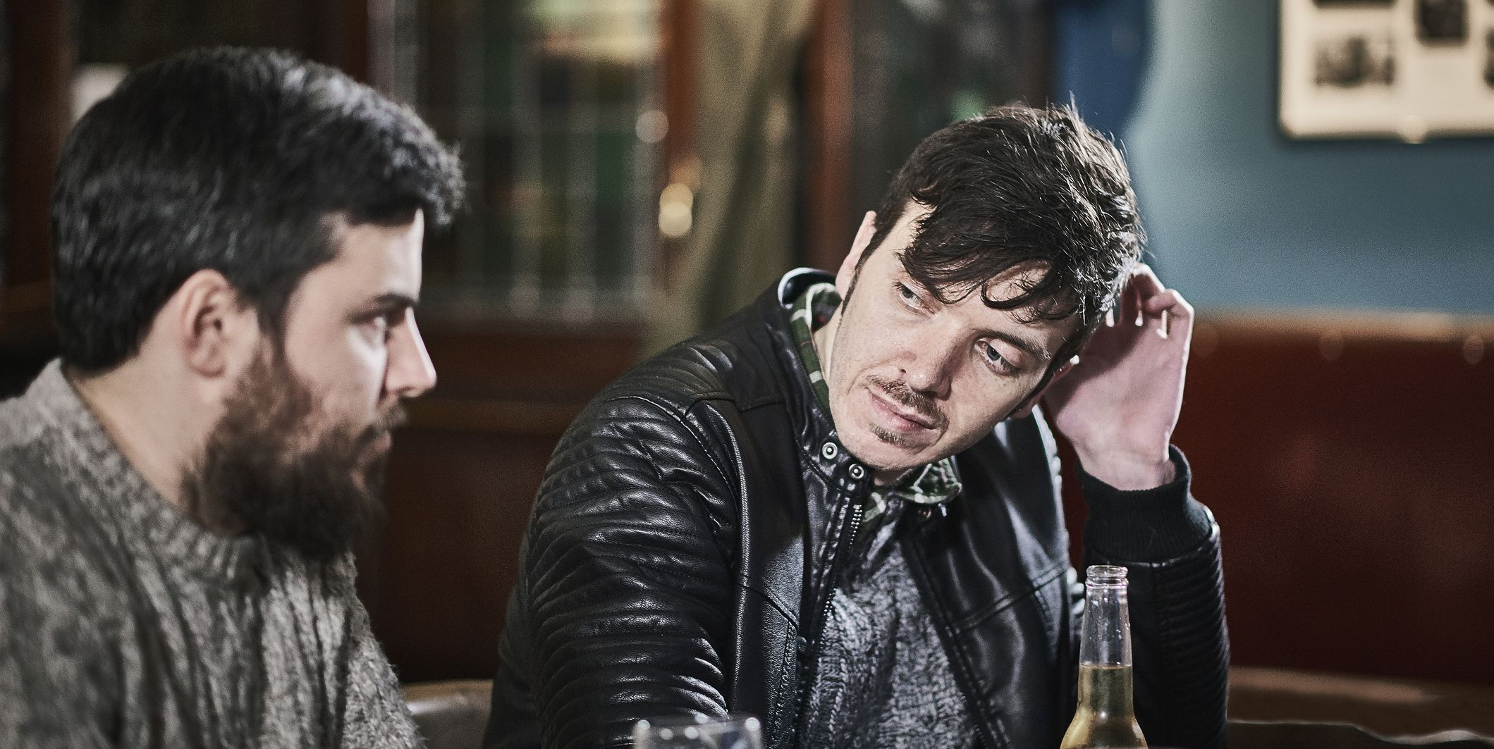 Two friends drinking together in a traditional British pub.