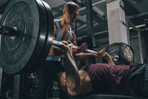 Two friends exercising bench press in gym