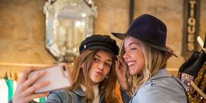 Two friends in shop, trying on hats, taking selfie, using smartphone