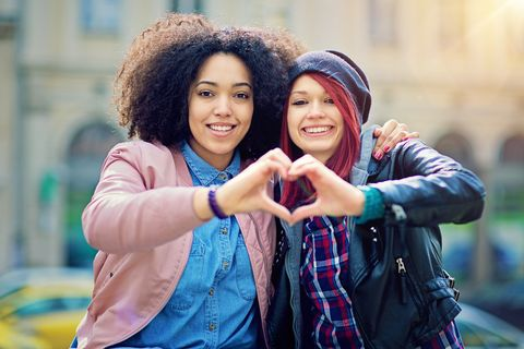 twee vriendinnen maken een hartje met hun handen