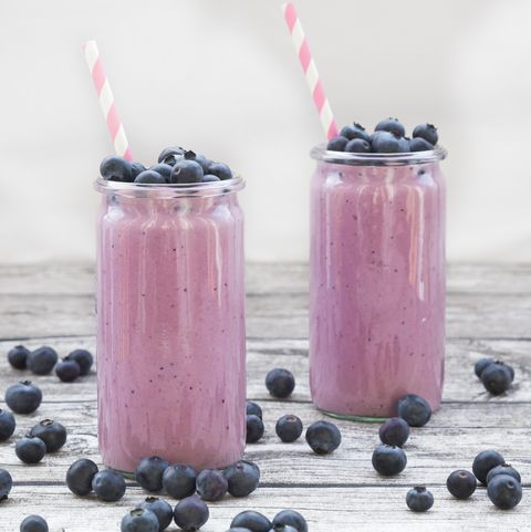 two glasses of blueberry smoothie and blueberries on wood