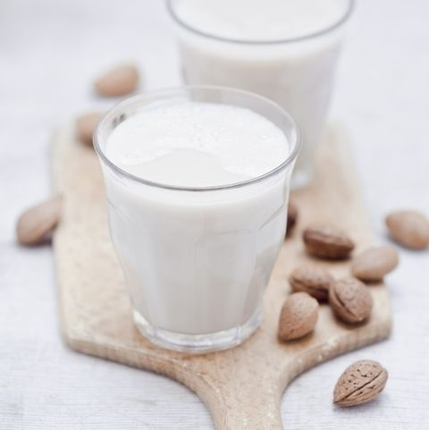 Two glasses of homemade almond milk and almonds on wooden board