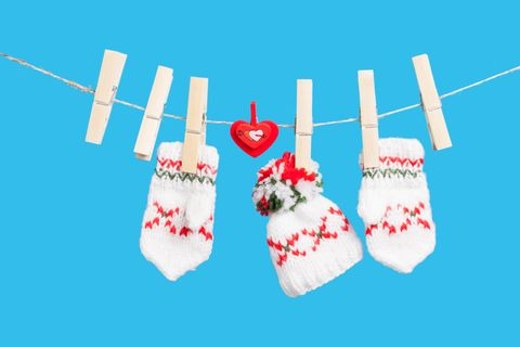 Two gloves, hat and heart on clothesline with clothespins, blue background