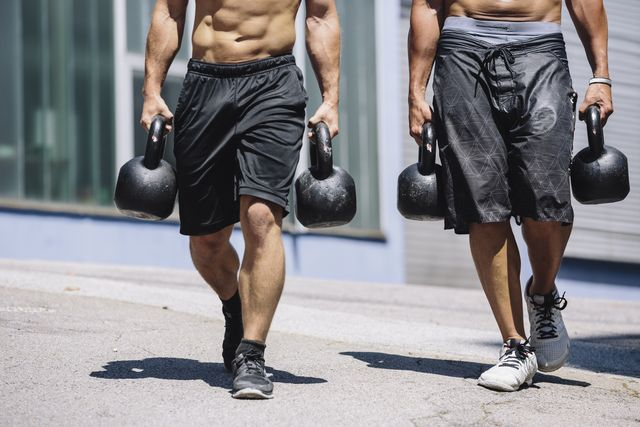 two gym athletes doing farmer's walk with kettlebells
