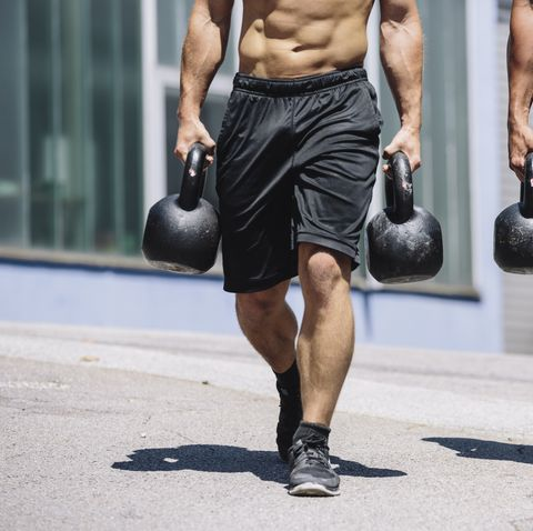 two gym athletes doing farmers walk with kettlebells