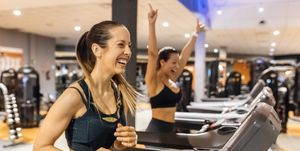 Two happy women working out in gym on a treadmil