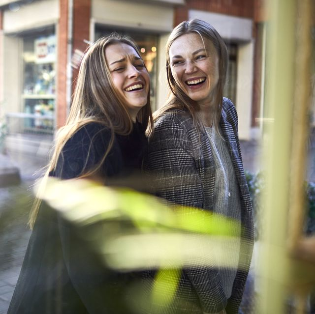 two happy young women behind shop window