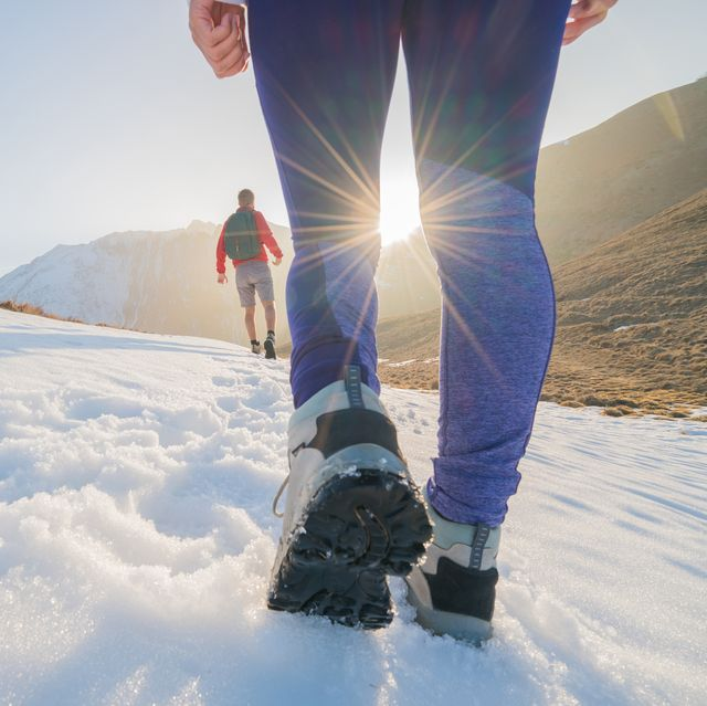 two hikers on snowy mountain trail
