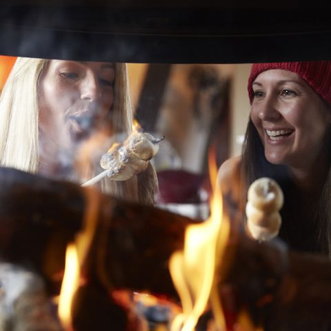winter date ideas - Two hip young women in cabin roasting smores