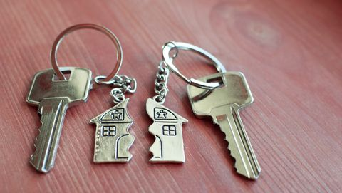 twee sleutels met een geplitste sleutelhanger in de vorm van een huis