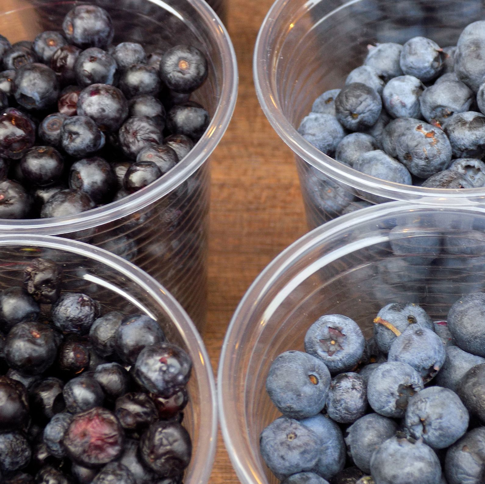 Two kind of Blueberries in the plastic glasses, on the market stand
