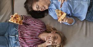 Two laughing young women lying down eating pizza together