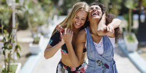 Two laughing young women outdoors in summer
