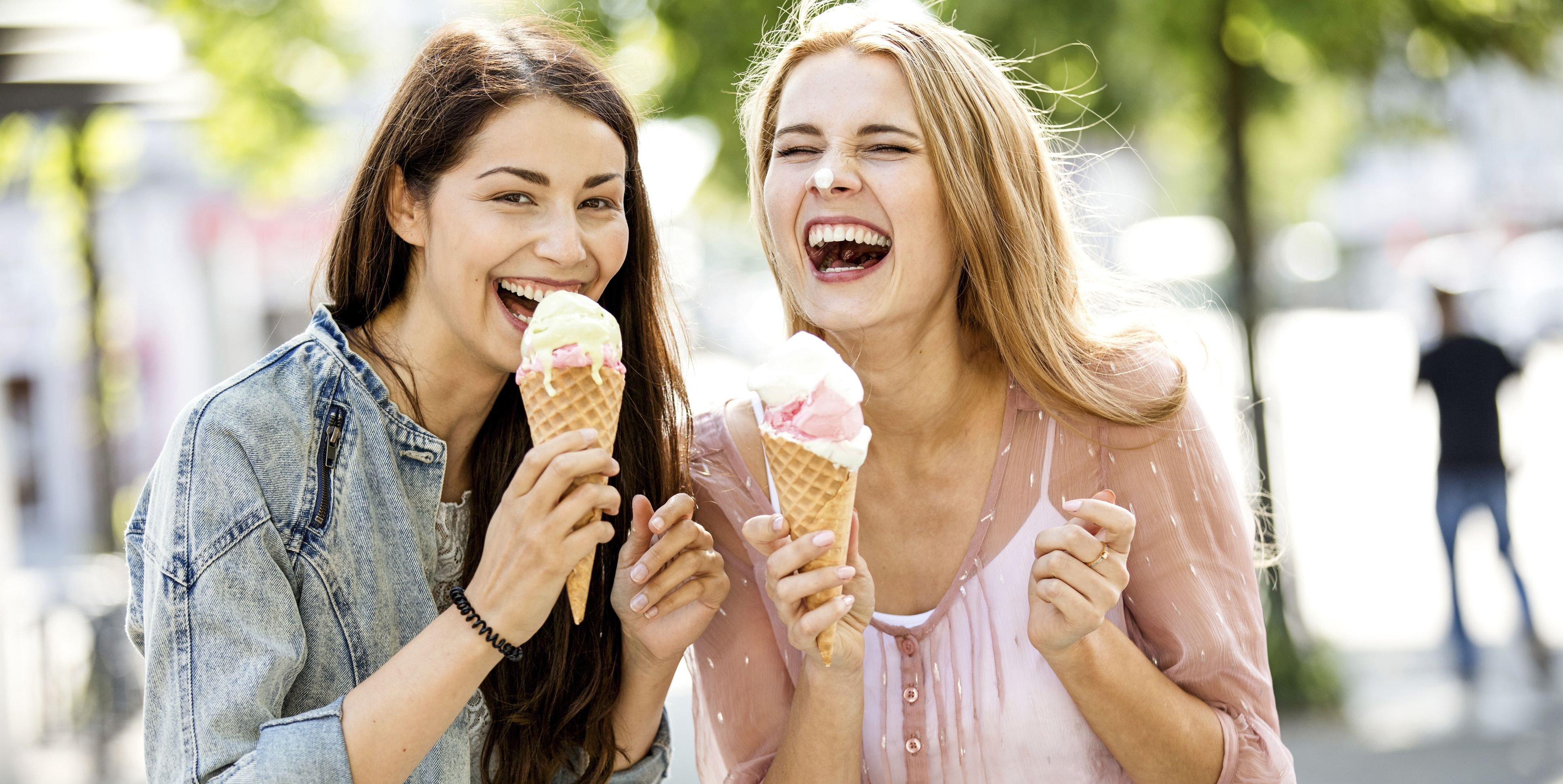 Two laughing young women with ice cream cones
