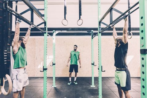 two male cross trainers training on exercise bar in gym