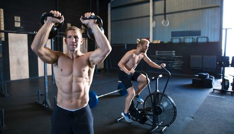 two men exercising in gymnasium, using kettlebells and using air resistance exercise bike