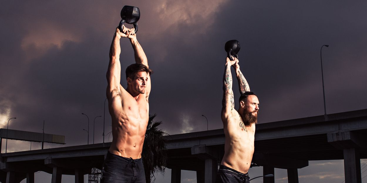 Two men training with kettlebells on gymnasium rooftop