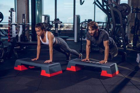 Two people doing push-ups on the step aerobics equipment