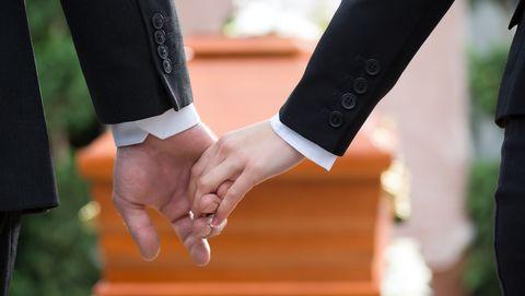 Twee mensen houden elkaars hand vast met een kist op de achtergrond