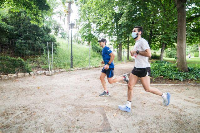 dos corredores aficionados corren por el retiro, uno de ellos con mascarilla