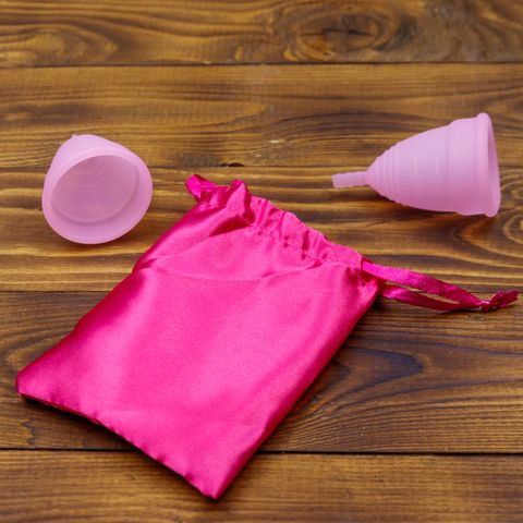 two pink reusable silicone menstrual cups and silk bag on wooden background concept of feminine hygiene, gynecology and health
