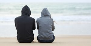Two sad teenagers sitting on the beach