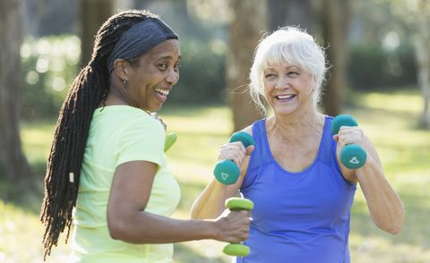 Two senior women exercising in park with hand weights