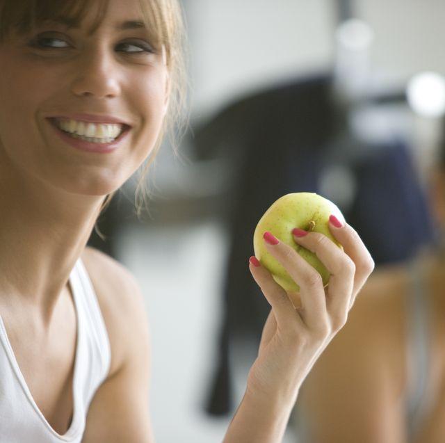 two smiling women eating apples defocused