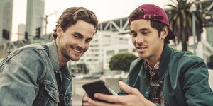 Two smiling young men sharing cell phone outdoors