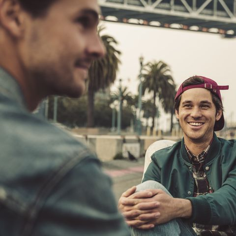 Two smiling young men sitting outdoors talking