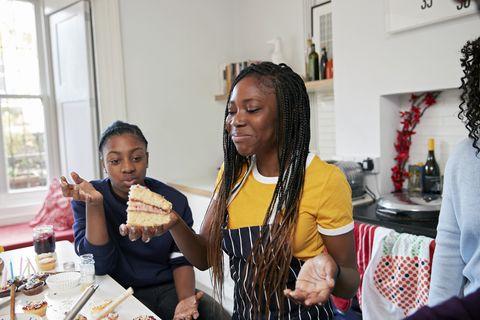 Two teenage girls (12-13, 14-15) eating cake in kitchen