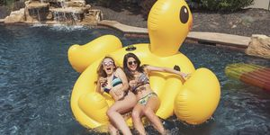 Two teenaged girls on rubber duck raft in swimming pool