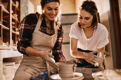 Two women at a pottery workshop making clay pots