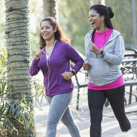 two women exercising together, power walking