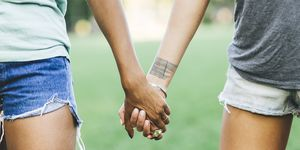 Two women holding hands in a park