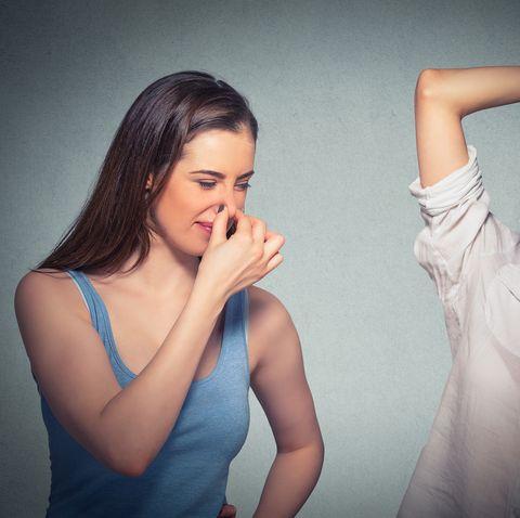 two women, one pinching nose something stinks, girls underarm