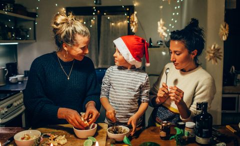 two women preparing christmas dinner with young boy