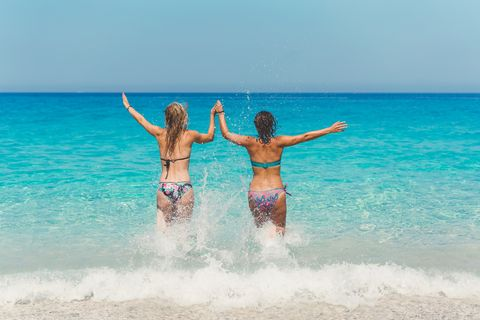 two women running in the blue mediterranean sea