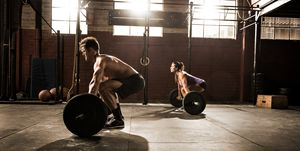Two young adults working out with barbells in gym