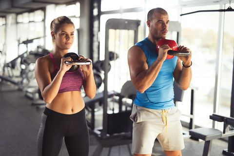 Two young athlete people doing kettlebell exercises at gym.