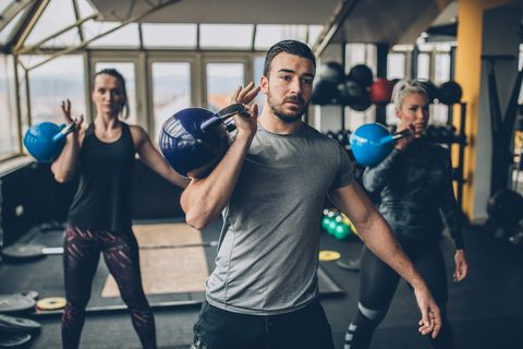 Two young fitness women exercise with kettlebells